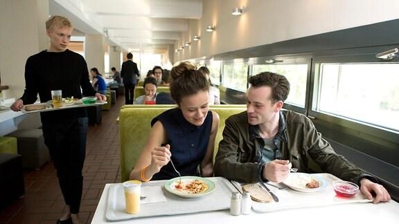 Trude (Lise Risom Olsen, li.) entdeckt in der Uni-Cafeteria die junge Lisa (Tinka Fürst) aus ihrem Traum, die sich mit ihrem Freund Florian (Florian Barholomäi, re.) zum Essen verabredet hat.