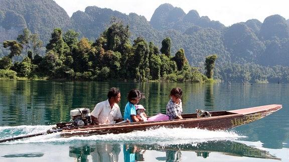 Eine Fischerfamilie fährt über den Khao-Sok-See zu einer religiösen Zeremonie in den Wald.