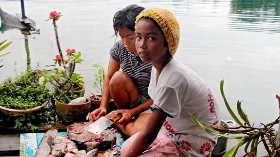 Die Töchter der Fischerfamilien am thailändischen Khao-Sok-See nehmen den Fang aus.