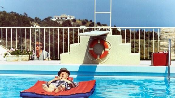 Egon Olsen (Ove Sprogöe) auf einer luftmatratze in einem Swiming-Pool.