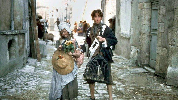 Tommi (Truan Munro) und seine Schwester (Karen Salt)stehen in der Straße einer sichtlich heruntergekommenen Stadtstraße.