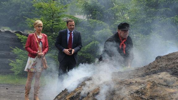 lara (Wolke Hegenbarth, l.) und Paul Kleinert (Felix Eitner, M.) stehen mit demKöhler Karl Brenner (Uli Krohm, r.) an einem Meiler.