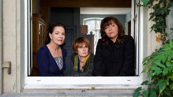 Helene (Gundi Ellert, rechts), Rosina (Gudrun Landgrebe) und Luise (Barbara de Koy) blicken aus einem Fenster.