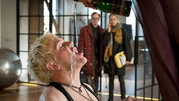 Rockstar Alexander Gromberg (Sebastian Bezzel, vorne) feiert bis zum Absturz. Seine Agentin Franzi (Susanne Bormann) und ihr Assistent Carl (Christian Näthe) sind bestürzt