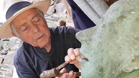 Bildhauer Volkmar Kühn bei der Arbeit. Polierte Bronzefiguren sind im ein Graus, weshalb er nach dem Guss immer auch mit Hammer und Meißel rangeht.