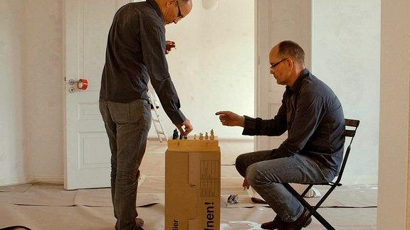 Zwei Männer spielen in einem kahlen Raum Schach.