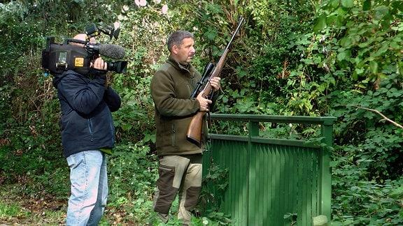 Stadtjäger Andreas Tietz  - mit Gewehr - in Begleitung des MDR-Kamerateams auf der Pirsch.