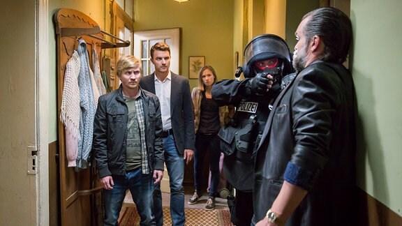 Jochen Berner (Ole Puppe) wird von einem Polizisten in SERK-Montur mit einer Pistole bedroht. Die Kommissare Henry Funck (Friedrich Mücke, m.), Maik Schaffert (Benjamin Kramme, l.) und Johanna Grewel (Alina Levshin)  beobachten mit grimmig-entschlossenem Blick das Geschehen.