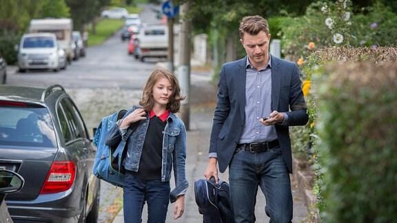 Henry Funck (Friedrich Mücke) geht mit seiner Tochter Claire (Maja Meinhardt) auf dem Fußweg einer weitgehend zugeparkten Sttaße.