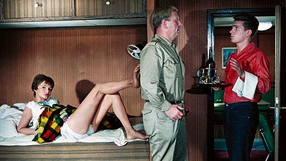 Der Kapitän (Günther Simon, Mitte) und der Bootsjunge Moses (Frank Schöbel) stehen  sich gegenüber. Moses trägt ein Tablett, au der eine Flasche Wein und Gläser stehen.  Eva (Anna Prucnal)  liegt mit verführerischer Pose im Kajütenbett.