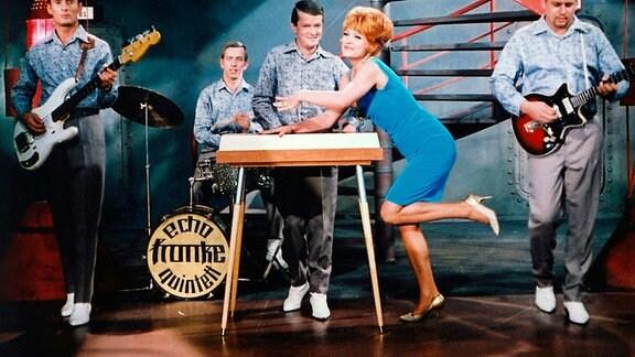 Sängerin Marylou (Eva-Maria Hagen) stützt sich auf einen Tisch. Neben ihr stehen verschidene Musiker mit Instrument.