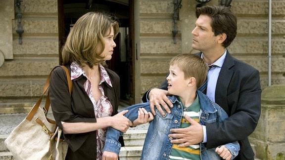 Oliver (Francis Fulton-Smith) und Lena (Daniela Buschhorn) streiten um Moritz (Maximilian Werner) auf der Straße vor dem Gericht.