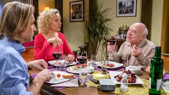 Michael (Erich Altenkopf, l.), Natascha (Melanie Wiegmann, rM.) iund ihr Vater (Hans-Jürgen Silbermann, r.) sitzen an einem gedeckten Toisch und essen.