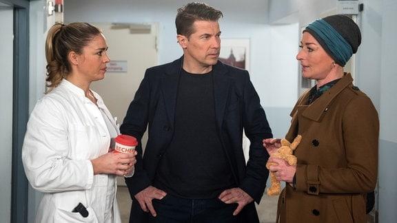 Gregor (Wolfram Grandezka, M.)  steht zwischen  Carla (Maria Fuchs, r.) und Britta (Jelena Mitschke, l.) in einem geschlossenen Raum.