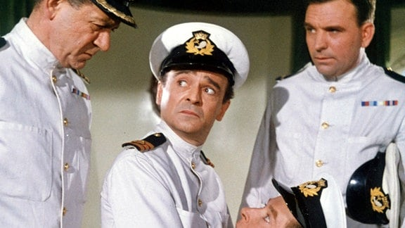 Misstrauisch beobachtet Kapitän Wellington Crowther (Sidney James, li.) zwei seiner neuen Crewmitglieder, Schiffsarzt Dr. Arthur Binn (Kenneth Connor, 2. v. li.) und den Ersten Offizier Leonard Marjoribanks (Kenneth Williams, kniend).