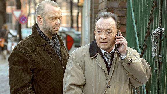 Journalist Döhring (Robert Gallinowski,links) steht hinter Ehrlicher (Peter Sodann), der telefoniert.