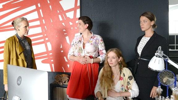 Die Agenturchefin Judith (Juliane Köhler, v. l. n. r.) stehtneben ihren Mitarbeiterinnen Marlene (Elena Uhlig) und Kati (Jessica Schwarz).  Linda (Pheline Roggan)  sitzt an einem Tisch. Mrarlene lächelt unnatürlich.  Lind und Kati blicken gequält.