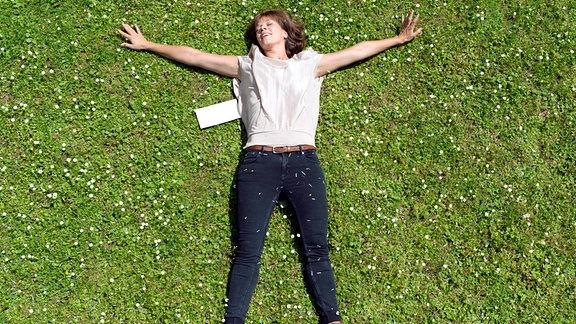Kati (Jessica Schwarz) liegt mit ausgebreitetem Armen auf dem Rücken im Gras.