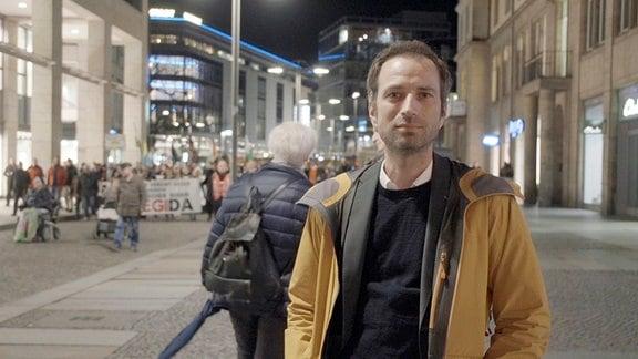 Axel Steier,(Pegida-Demonstration im Hintergrund)