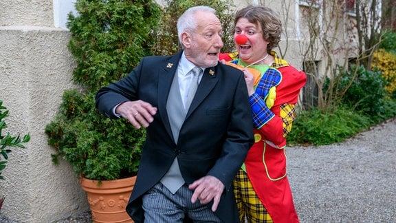 Der als Clown verkleidete Bela (Franz-Xaver Zeller, r.) erlaubt sich einen Spaß mit Alfons (Sepp Schauer, l.).