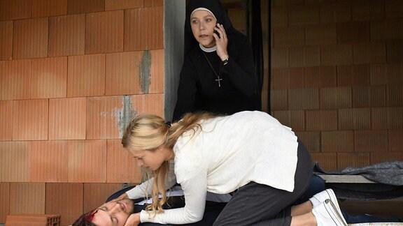 Nick Vogel (Frederik Götz, l.) liegt am Boden  und Jessy Rainer (Anna Platen, M.) beugt sich über ihn. Hanna ruft per Handy den Krankenwagen.