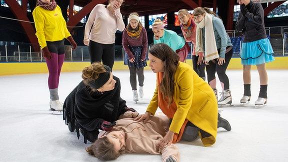 Solveig Dietze (Linda Stockfleth, liegend) liegt auf dem Eis.. . Ihre Mutter Jutta (Judith Rosmair, li.) und Arzu Ritter (Arzu Bazman, re.), die gerade mit ihren Söhnen zu einer Schnupperstunde vorbeischaut, beugen sich über sie.