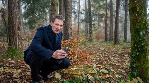 Christoph (Dieter Bach) kniet in einem Wald und hat ein Hqandy in der Hand.