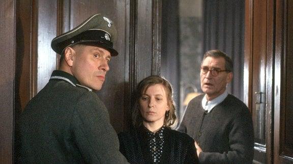SS-Müller (Michael Kind, l.) kommt zu Eva (Dagmar Manzel, M.) und Victor Klemperer (Matthias Habich, r.), um alle Medikamente im Judenhaus zu beschlagnahmen.