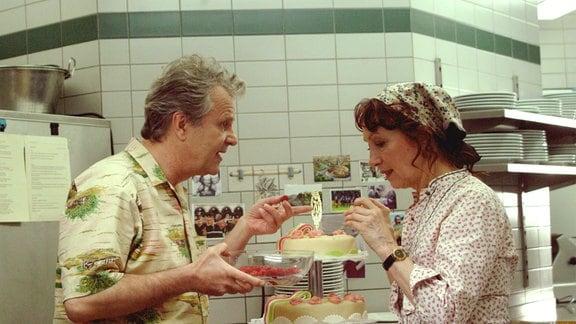 Koch Jockl (Peter Sattmann) und seine Partnerin Rosaria (Marlen Diekhoff) bereiten die Geburtstagstorte vor