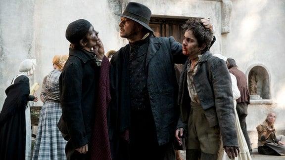 Luini (Moritz Bleibtreu) droht den schwarzen Brüdern Giorgio (Fynn Henkel) und Pietro (Kilian Marcon).