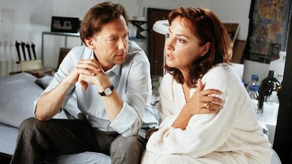 Annabelle Schrader (Simone Thomalla) und ihr Mann Friedrich (Stephan Schwartz) sitzen - angezogen - auf einem Bett.