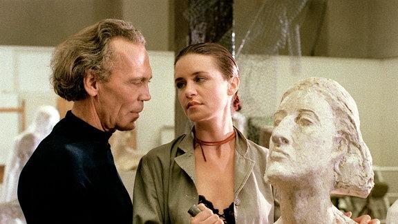 Professor Paulus (Peter Gavajda) und Studentin Sabrina Pohl (Patricia Schäfer) an einer Porträtbüste aus unkanntem Material. Sie halten beide Spatel in der Hand und blicken sich an.