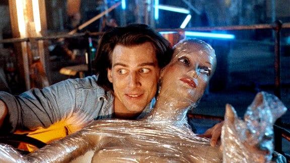 Der Künstler Dirk Raabe (René Steinke) hält eine fast wwagerecht nach hinten geneigte Nacktpuppe, die von einem eng anliegenden transparewnten Kunststoff umhüllt ist.