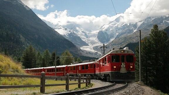 Ein Zug der Bernina-Bahn scheint aus der Bergmassiven der Alpen herauszufahren.