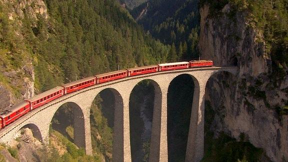 Markantestes Motiv der Albula-Linie. In 65 Metern Höhe überquert das Viadukt, über gas gerade ein elektrisch betriebener 1000-mm-Schmalspurzug in der markanten roten Farbgebung fährt,  eine Schlucht und endet an einem Tunneleingang in luftiger Höhe. Unmittelbar nach Überquerung des Viadukts wird der Zug in einen hier schon sichbaren Tunnnel einfahren.