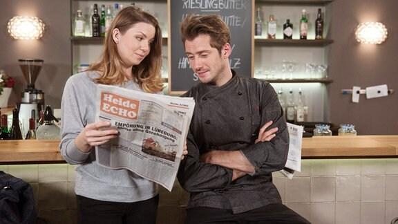 """Judith (Katrin Ingendoh, l.) zeigt Alex (Philipp Oliver Baumgarten, r.) die Pressekritik über das neu benannte """"Stint""""."""