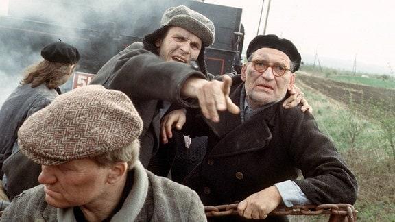 Victor Klemperer (Matthias Habich, r.) taucht unbemerkt im Flüchtlingsstrom unter. Ein Unbekannter (Alexander Hoechst, M.) macht ihn auf eine kleine Bahnstation voller Flüchtlinge aufmerksam.