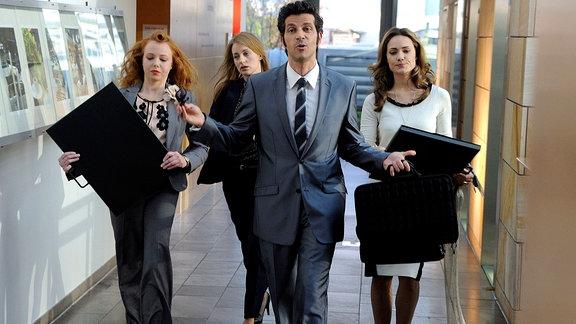 Eine männliche Person geht - gefolgt von drei jüngeren Damen - durch einen Gang mit Ausstellungstafeln