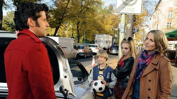 Moritz (Pasquale Aleardi, links) steht mit Nina (Tanja Wedhorn, rechts) mit deren beiden Kindern Max (Tom Hoßbach) und Jule (Camares Amonat) neben einem Krraftwagen.