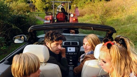 Moritz (Pasquale Aleardi) sitzt mit Nina (Tanja Wedhorn, rechts) und ihren beiden Kinder Max (Tom Hoßbach) und Jule (Camares Amonat) sin einem offen Personenkraftwagen. Vor ihnen fährt ein Traktor älterer Bauart.