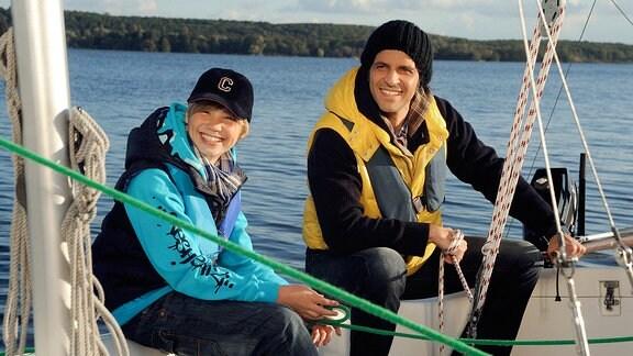 Moritz (Pasquale Aleardi, rechts) und Max (Tom Hoßbach) sitzen auf der Bordwand eines Bootes.