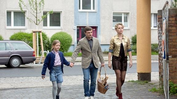 Martin Kupfer (Florian Lukas, M.), Tochter Anna (Ziva-Maria Faske, l.) und seine Westberliner Freundin Katja (Lisa Wagner, r.) laufen auf einer städtisch wirkenden Straße.