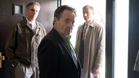 Hans Kupfer (Uwe Kockisch, M.) blickt in Richtung Kamera, Neben ihm stehen zei Herren.