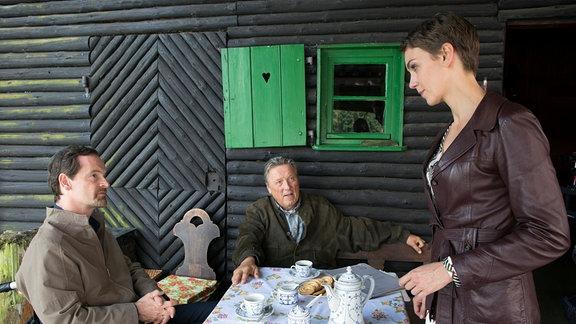 Generalleutnant a.D. Gaucke (Hansjürgen Hürrig, M.) konfrontiert Falk (Jörg Hartmann, l.)  sitzen an einem Kaffeetisch vor einem Holzhaus. Doreen Hager (Manja Kuhl, r.)  steht dabei.
