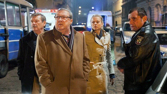 Die Kommissare Schmücke (Jaecki Schwarz, 2. von links), Schneider (Wolfgang Winkler, links) und Nora Lindner (Isabell Gerschke, 2. von rechts) stehen mit uniformierten Kolegen auf einer Straße mit städtischer Bebauung.