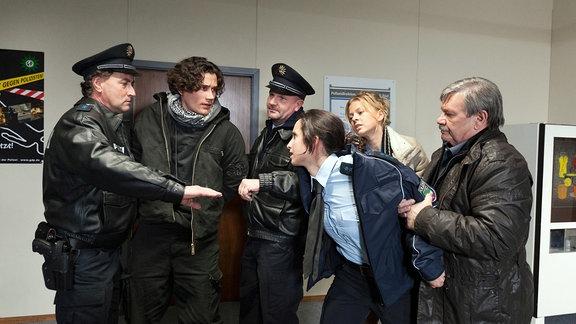 Zei uniformierte Polizisten führen in einer Bildergalerie einen jungen Herren ab. Eine uniformierte Polizistin scheint sich auf ihn zu stürzen; Kommissar Schneider (Wolfgang Winkler, rechts) und Nora Lindner (Isabell Gerschke, 2. von rechts hinhten) halten sie gewaltsam zurück.