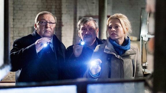 Schmücke (Jaecki Schwarz, links), Schneider (Wolfgang Winkler, mitte) und Nora Lindner (Isabell Gerschke, rechts) leuchten mit Taschenlampen in Richtung Kamera.