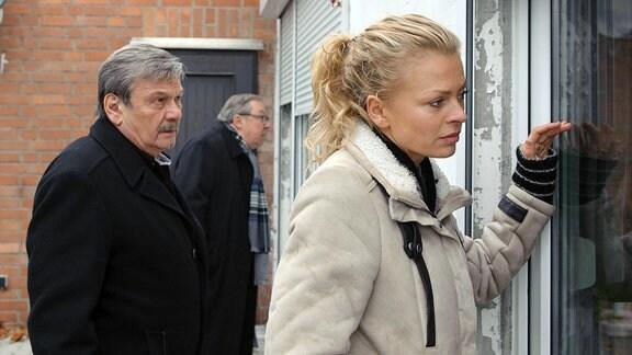Schmücke (Jaecki Schwarz, mitte hinten), Schneider (Wolfgang Winkler, links) und Nora Lindner (Isabell Gerschke, rechts) blicken druch die Fenster in eine Wohnung.