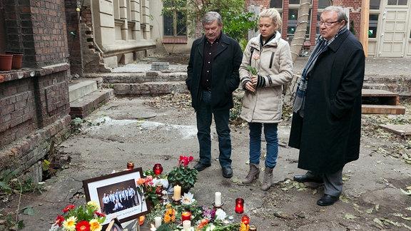 Schmücke (Jaecki Schwarz, rechts), Schneider (Wolfgang Winkler, links) und Nora Lindner (Isabell Gerschke, mitte)  strehen in einem Bof. Vor ihnen Blumen, Kerzen un Fotos.
