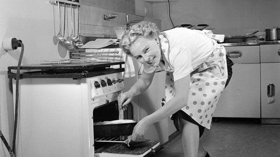 Eine Frau nimmt einene Backform aus dem Küchenherd.